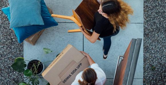 En kvinna som bär ut möbler när hon flyttar hemifrån.