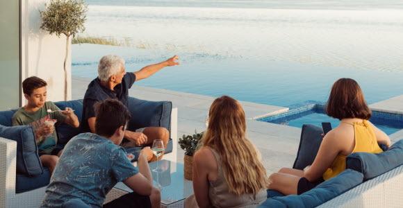 En familj som flyttat utomlands sitter i en soffgrupp och blickar ut mot havet.