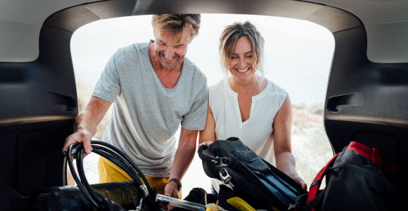 En skrattande kvinna och man lastar av dykutrustning ur bakluckan på en bil.
