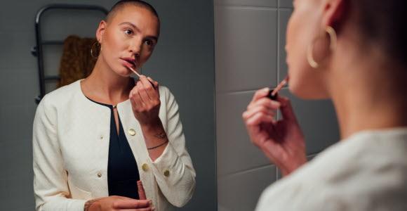 En kvinna som står och sminkar sig framför en spegel.
