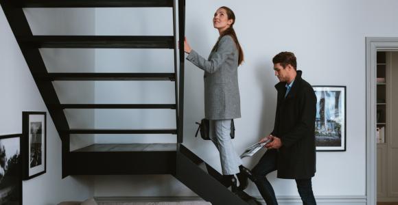 Ett par som är på bostadsvisning och går upp för trappan i en etagelägenhet.