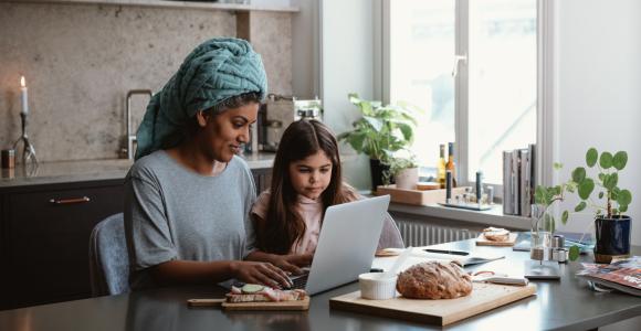 En kvinna och hennes dotter som sitter framför datorn i köket.